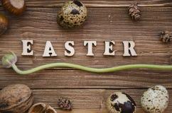 Ostern-Buchstabe auf dem hölzernen Hintergrund verziert mit Nüssen, Blumen und Eiern Stockfotografie