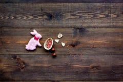 Ostern compisition Ostern-Bonbongeschenk Schokoladeneier nähern sich Plätzchen in Form von Osterhasen auf dunklem hölzernem Hinte lizenzfreie stockfotos