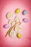 Ostern, das mit Frühlingsblumen, -ei und -kuchen auf rosa Hintergrund verfasst Lizenzfreie Stockfotografie