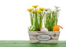 Ostern-Dekoration - Blumen in der Holzkiste mit bunten Eiern auf dem hölzernen Hintergrund Lizenzfreie Stockbilder