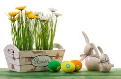 Ostern-Dekoration - Blumen in der Holzkiste und in den bunten Eiern auf dem hölzernen Hintergrund Stockfotos