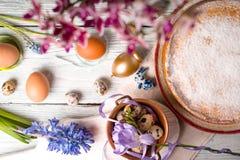 Ostern-Dekoration, Blumen und Deutscher Ostern backen auf der weißen Draufsicht des Holztischs zusammen Stockfoto