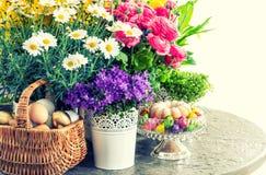 Ostern-Dekoration mit Blumen, Eiern und Kuchen Abbildung der roten Lilie Stockbilder