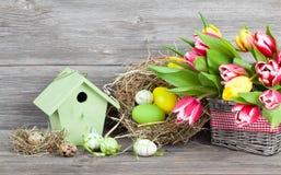 Ostern-Dekoration mit Eiern, Vogelhaus und Tulpen. hölzernes backgr Stockfotos