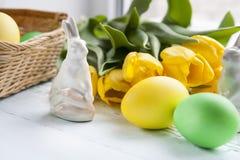 Ostern-Dekoration mit gelben Tulpen, keramischen Kaninchen und farbigen Eiern über hellem Hintergrund Stockbilder