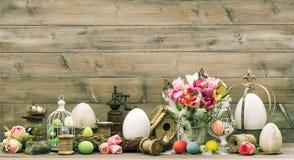 Ostern-Dekoration mit rosa Tulpenblumen und farbigen Eiern Lizenzfreies Stockfoto