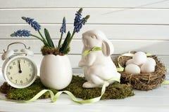 Ostern-Dekoration mit weißem Kaninchen, Frühlingsblumen, Wecker und ländlichen Eiern Östliches Häschen Stockbilder