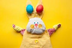 Ostern-Dekorationen von einem handgemachten Spielzeugkaninchen und von bunten Eiern auf einem orange Hintergrund Lizenzfreies Stockfoto