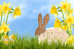 Ostern-Dekorations-hölzernes Kaninchen mit Narzissen Stockbilder