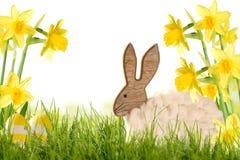 Ostern-Dekorations-hölzernes Kaninchen mit Narzissen Stockfotos