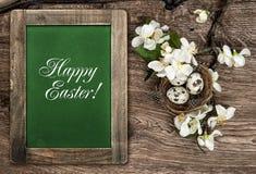 Ostern-Dekorationseier, -blumen und -tafel Lizenzfreie Stockfotos