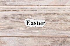 Ostern des Wortes auf Papier Konzept Wörter von Ostern auf einem hölzernen Hintergrund Lizenzfreie Stockfotografie