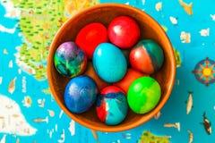 Ostern färbte die Eier, gelegen in einem Lehmvase auf dem Hintergrund einer Karte der Welt Lizenzfreies Stockfoto
