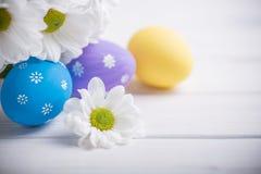 Ostern färbte Eier mit Blumen auf weißem hölzernem Hintergrund Stockbilder