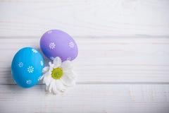 Ostern färbte Eier mit Blumen auf weißem hölzernem Hintergrund Stockfotos
