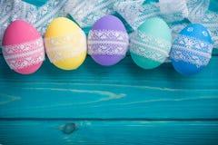 Ostern färbte Eier mit Spitzeband auf blauem hölzernem Hintergrund Stockfoto
