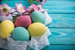 Ostern färbte Eier mit Spitzeband und Blumen auf blauem hölzernem Hintergrund Stockfoto