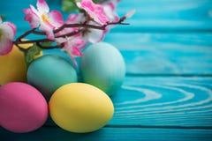 Ostern färbte Eier mit Spitzeband und Blumen auf blauem hölzernem Hintergrund Lizenzfreie Stockbilder
