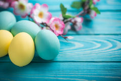 Ostern färbte Eier mit Spitzeband und Blumen auf blauem hölzernem Hintergrund Stockfotos