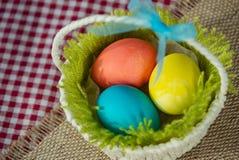 Ostern f?rbte Eier in einem Korb auf einer Segeltuchserviette und einer karierten Tischdecke stockbilder