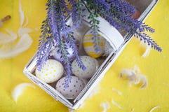 Ostern, farbige Eier, Gelb, Weiß, in einem Korb, Federn, Blumen, Lavendel, purpurrote Blumen stockfotografie