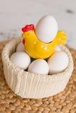 Ostern-Feier zu Hause Eine helle gelbe Henne mit weißen Bio-Eiern in einem gestrickten Topf Stockfotografie