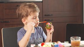 Ostern-Feierkonzept Glücklicher kleiner Junge, der Ostereier für Feiertag verziert stock footage
