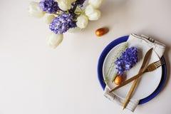 Ostern-Feiertagsgrußkarte, Speisetisch mit Platte, goldenes Tischbesteck, gemalte Eier und Hyazinthenblume auf weißem Hintergrund Lizenzfreies Stockbild