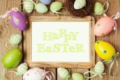 Ostern-Feiertagskonzept mit Eidekorationen und Fotorahmen auf hölzernem Hintergrund Stockfotografie