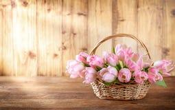 Ostern-Feiertagskorb mit schönen rosa Tulpen stockbilder