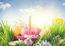 Ostern-Feiertagsszenenhintergrund Traditionelles gemaltes buntes Gras der Eier im Frühjahr über blauem Himmel Lizenzfreie Stockfotos