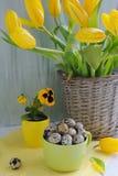 Ostern-Feiertagszusammensetzung mit gelben Tulpen auf Holztisch Stockfoto