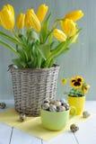 Ostern-Feiertagszusammensetzung mit gelben Tulpen auf Holztisch Stockfotos