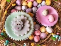 Ostern-Festlichkeiten, gefrorene kleine Kuchen und Ostereier, flache gelegte Nahrungsmittelphotographie stockfoto