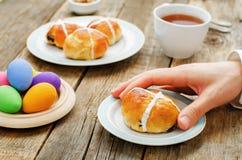 Ostern-Frühstücks-Mann, der das Brötchen mit einem Kreuz hält Stockbild