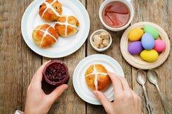 Ostern-Frühstücks-Mann, der das Brötchen mit einem Kreuz und ein Glas von hält Stockbilder