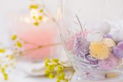 Ostern-Gedeck, Details, Schokoladeneier im eleganten Glas, Kerze, Blumen Lizenzfreie Stockfotos
