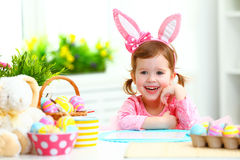 ostern glückliches Kindermädchen mit den Häschenohren mit farbigen Eiern und f Stockbilder