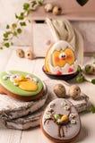 Ostern-Grünplätzchen mit gemaltem Osterhasen und ausgebrütetem Huhn nahe Wachteleiern, dekorativem Buffet und Serviette stockbild