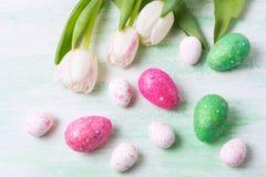 Ostern-Gruß mit weißen Tulpen-, Grünen und rosafunkelneiern stockbild