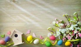 Ostern-Hintergrund mit bunten Eiern und Frühling blüht lizenzfreies stockbild