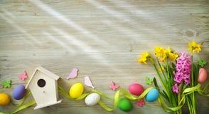 Ostern-Hintergrund mit bunten Eiern und Frühling blüht lizenzfreie stockbilder