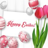 Ostern-Hintergrund mit farbigen Eiern, roten Tulpen und Grußkarte über weißem Holz Stockfotos