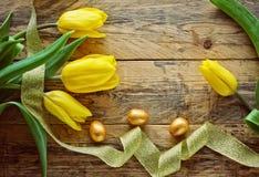 Ostern-Hintergrund mit gelben Tulpen, goldene Eier Lizenzfreie Stockfotografie