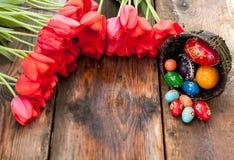 Ostern-Hintergrund mit Ostereiern und roten Tulpen Lizenzfreies Stockfoto