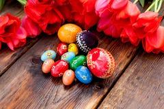 Ostern-Hintergrund mit Ostereiern und roten Tulpen Lizenzfreie Stockbilder