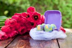 Ostern-Hintergrund mit Ostereiern und roten Tulpen Stockfotos