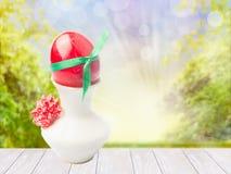 Ostern-Hintergrund mit weißem Holztisch, Ei in der Schale und Frühling gestalten mit bokeh landschaftlich lizenzfreies stockbild