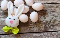 Ostern-Kaninchen und -eier auf Holztisch Lizenzfreies Stockfoto