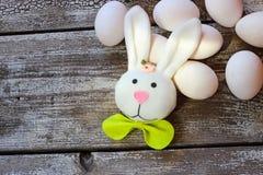 Ostern-Kaninchen und -eier auf Holztisch Lizenzfreie Stockbilder